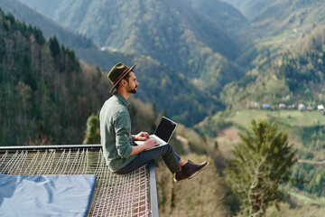 Obraz Young man freelancer traveler wearing hat anywhere working online using laptop and enjoying mountains view - fototapety do salonu