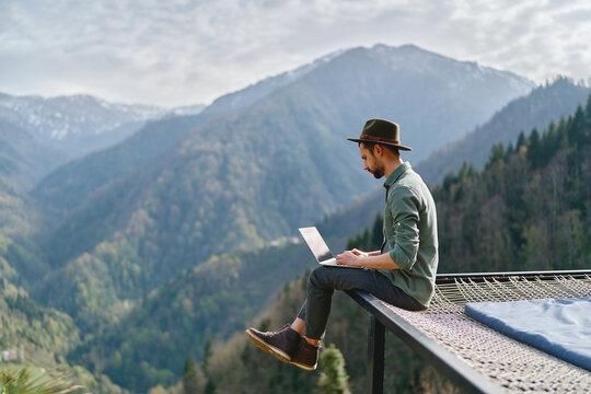 Young man freelancer traveler wearing hat anywhere working online using laptop and enjoying mountains view