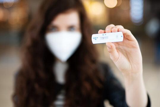 Eine junge Frau mit einem negativen Corona-Schnelltest, Testpflicht in öffentlichen Bereichen