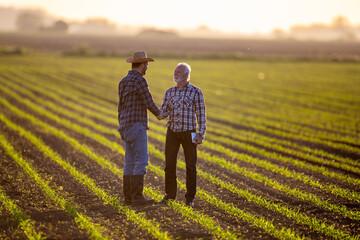Fototapeta Two men shaking hands in corn field reaching agreement. obraz