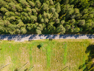 Fototapeta Aerial view of a rural landscape of woodland and grassland separated by a road in the middle