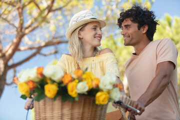 Fototapeta loving couple on summers day by a bicycle with flowers obraz