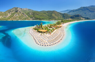Aerial view of sea bay, sandy beach with umbrellas, trees, mountain at sunny day in summer. Blue lagoon in Oludeniz, Turkey. Tropical landscape with island, white sandy bank, blue water. Top view - fototapety na wymiar