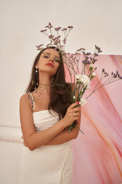 A girl in a white dress with small mauve flowers poses in a light interior. Fashion model studio portrait. Caucasian brunette woman with long hair and perfect make-up
