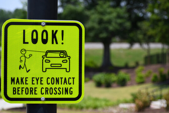 Bright yellow pedestrian crossing make eye contact before crossing look