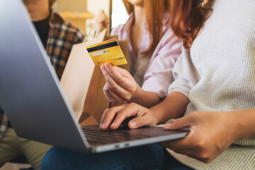 Group of young people using laptop and credit card for shopping online together - fototapety na wymiar