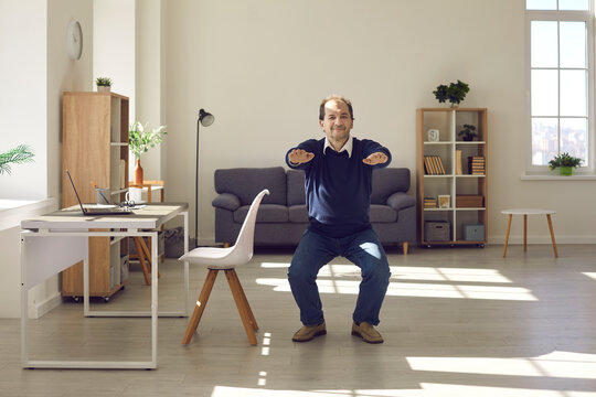 Senior man squatting in the living-room. Happy energetic mature businessman doing fitness warm up exercise during working day in home office. Concept of workplace workout for keeping fit and healthy