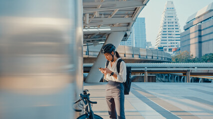 Fototapeta Smile asian businesswoman with backpack use smart phone look camera in city stand at street with bike go to work at office. Sport girl use phone for work. Commute to work, Business commuter in city. obraz