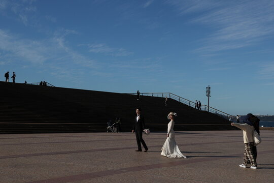 A couple poses for wedding photos in front of the Sydney Opera House steps in Sydney