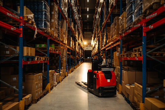 Rows of shelves with goods and forklift