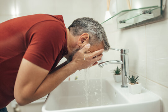 Adult man, using hands, washing face with water.