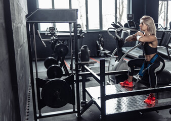 Fit Woman practicing squats in an exercise machine in the gym. Lifestyle - fototapety na wymiar