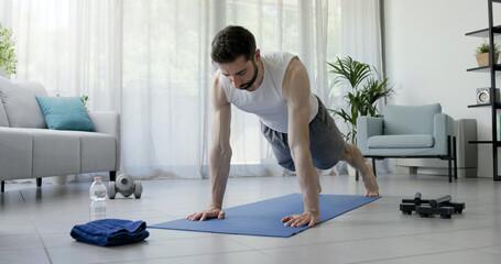 Obraz Athletic man doing push ups at home - fototapety do salonu