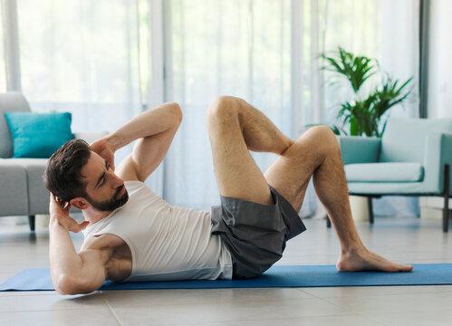 Athletic man exercising at home