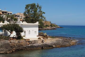 Stary biały budynek przy kamienistym brzegu nad morzem na Krecie, Grecja