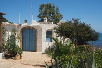 Stary biały budynek z niebieskimi drzwiami nad morzem na Krecie, Grecja
