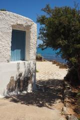 Fototapeta Stary biały budynek z niebieskimi drzwiami nad morzem na Krecie, Grecja  obraz