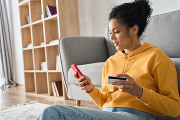 Young adult African American female consumer holding credit card and smartphone sitting on floor at home doing online banking transaction. E commerce virtual shopping, secure mobile banking concept. - fototapety na wymiar