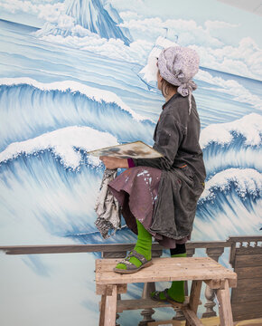 Mature Woman Artist Paints A Mural On A Marine Theme On The Wall