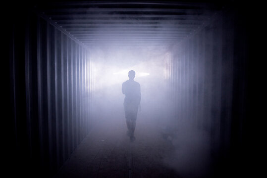 Silhouette of a man walking in a dark tunnel to the light