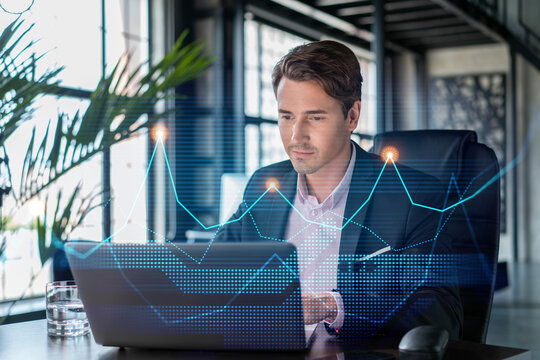 Handsome businessman in suit at workplace working with laptop to optimize trading strategy at corporate finance fund. Forex chart hologram over office background
