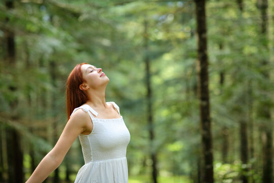 Woman in white breathing fresh air in a forest
