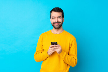 Young caucasian man over isolated blue background sending a message with the mobile