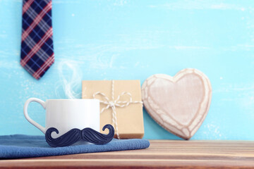 Fototapeta image of fathers day composition with hot cup of coffee over table and blue background obraz