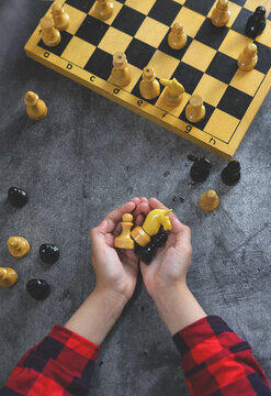 International Chess Day. A small child's hands hold chess pieces next to a chessboard on a dark background. Table games. Family and children's leisure. Vertical. Layout