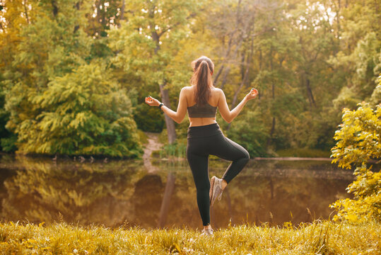 Photo of young beautiful sport woman exercising yoga outdoor in park near lake, peaceful concept