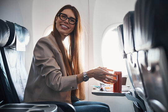 Optimistic woman reaching for soda can on tray table