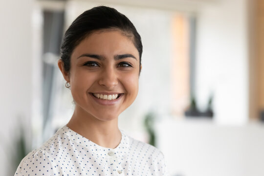 Head shot portrait of confident successful smiling Indian businesswoman standing in office, happy entrepreneur employee executive looking at camera, posing for corporate photo, profile picture