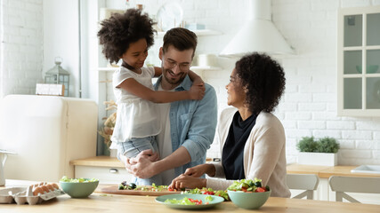 Fototapeta Smiling young multiracial mom and dad cook healthy delicious vegetarian salad with ethnic small daughter. Happy multiethnic family with girl child have fun prepare food in kitchen. Adoption concept. obraz