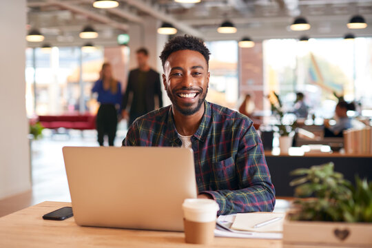 Portrait Of Smiling Businessman Sitting At Desk With Laptop In Modern Open Plan Office
