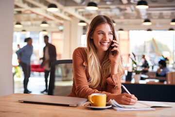 Fototapeta Young Businesswoman Sitting At Desk On Phone Call In Modern Open Plan Office obraz