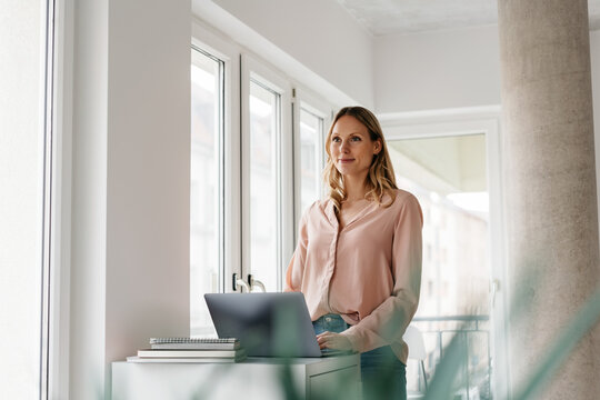 Young woman working at a laptop standing staring ahead with a thoughtful smile