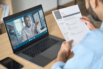 Fototapeta Young indian confident businessman holding cv talking to male black man potential employee hiring for job. Virtual video call between employer and manager worker. Remote recruitment work concept. obraz