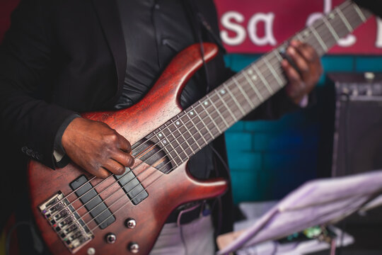 Concert view of an african-american musician with electric bass guitar player during band performing rock music,  bassist player on stage