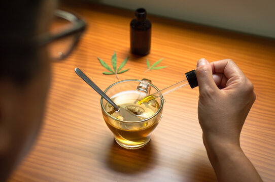 Woman pouring CBD oil in a natural infusion. Using CBD, natural remedy made with cannabis.