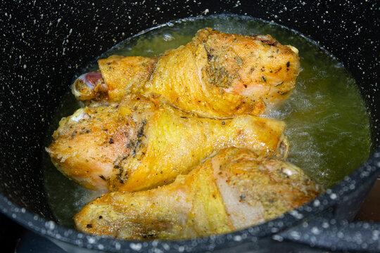 Chicken legs are fried in oil