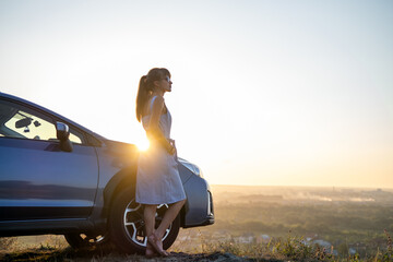 Obraz Happy young woman driver in blue dress leaning on her car enjoying warm summer day. Travelling and vacation concept. - fototapety do salonu