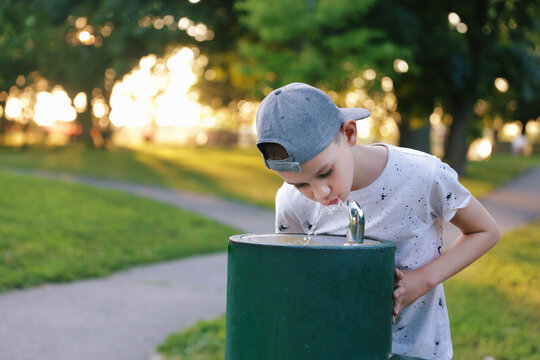 Boy drinks tap water from public drinking fountain. Free space for your text