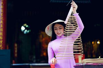 Vietnamese woman in traditional dress praying