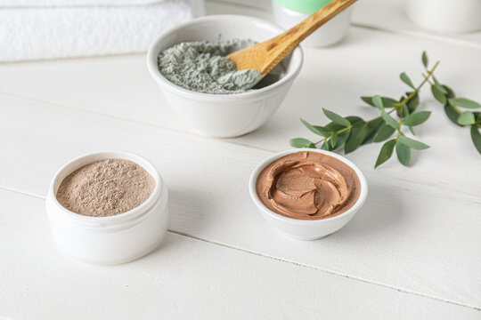 Bowls with cosmetic clay on light wooden background