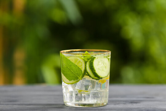 Glass of cucumber lemonade on table outdoors