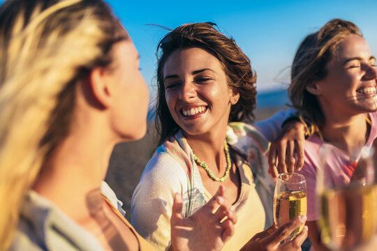 Happy young women drinking champagne at bachelorette party on the beach