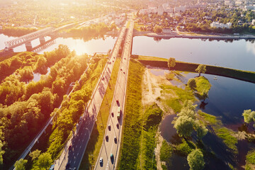 Cars traffic on bridge over the river, aerial view. Top view of bridge over Sozh river in Gomel, Belarus - fototapety na wymiar