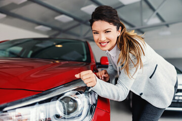 Fototapeta Smiling female car dealer standing in car salon and rubbing headlights with her sleeve while looking at camera. obraz