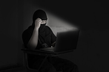 Hacker in black mask using laptop for crime cyber attack network security and stealing personal data infomation. - fototapety na wymiar