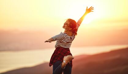 Fototapeta Happy woman  dances, jump, rejoices, laughs  on sunset in nature obraz